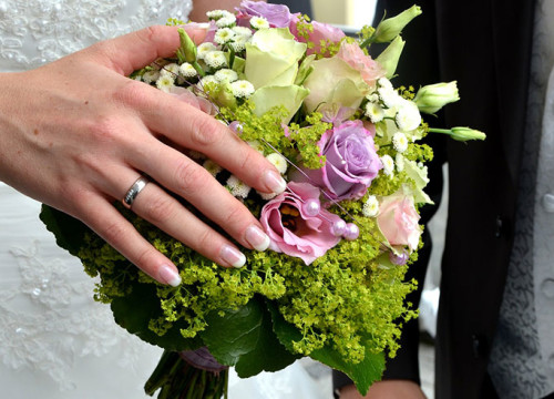Bride and groom with bride holding a pink, purple and white wedding bouquet with french manucured hand and wedding ring