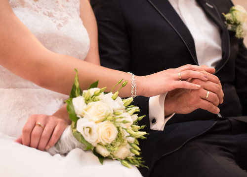 Bride and groom sat down wearing wedding rings holding hand, bride has a white rose wedding bouquet on her lap