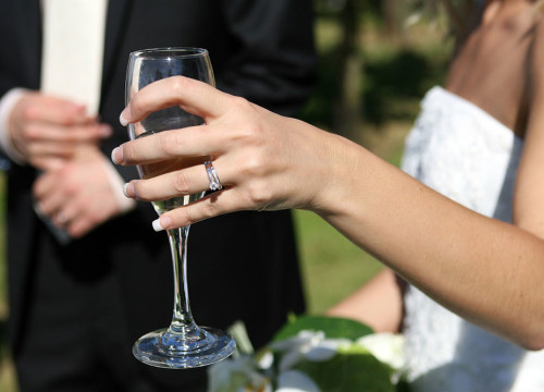 Bride's hand with wedding and engagement rings, french manucure and holding a champagne flute in garden
