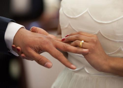 Bride sliding wedding ring on groom's finger, wearing wedding dress, wedding ring and red nail varnish