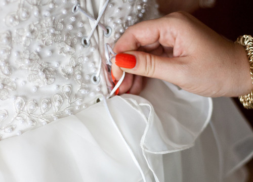 Back of a bride's wedding dress corset being laced up by woman's hand in red nail varnish