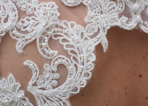 Lace, pearl and sequin details on the back of a bride's white wedding dress