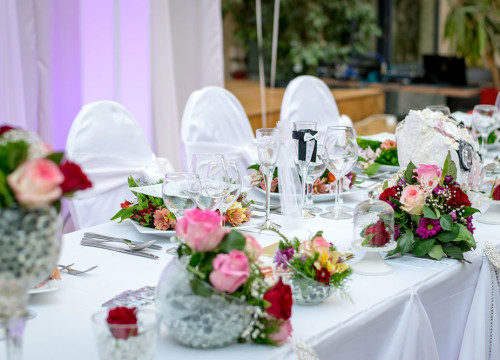 Wedding banquet table with white table cloth, pink, red and purple flower bouquets and red roses under glass bells
