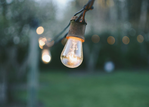 Close-up of a rustic light bulb hanging on a decorative wire ar an outdoor wedding venue