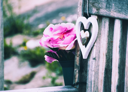 White and silver wooden love heart hanging from a wooden bench on which a pink flower bouquet is placed
