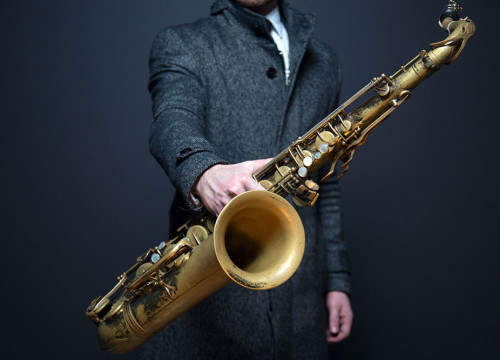 Man in long dark grey coat holding a golden saxophone against a dark blue wall for wedding band