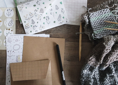 Botanical patterned wedding stationery including envelopes and cards, a black pen an grey knitted wool