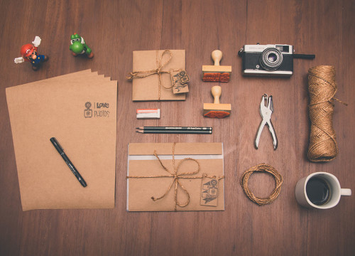 Wedding stationery on wooden table including envelopes, cards, stamps, string, camera, coffee cup, Super Mario, Koopa and pencils