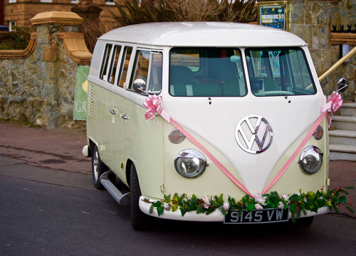 Light green VW campervan dressed as honeymoon car with pink ribbon and flowers, parked by town hall