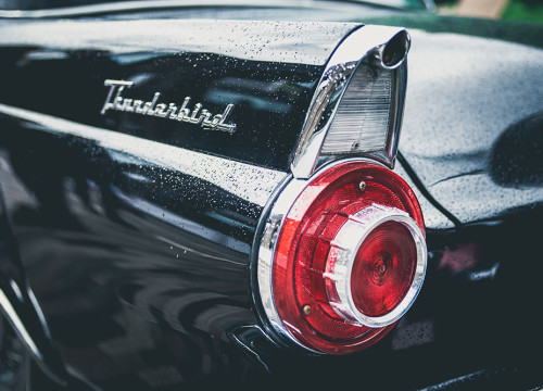 Back left light of a black Thunderbird wedding car under the rain at a wedding ceremony