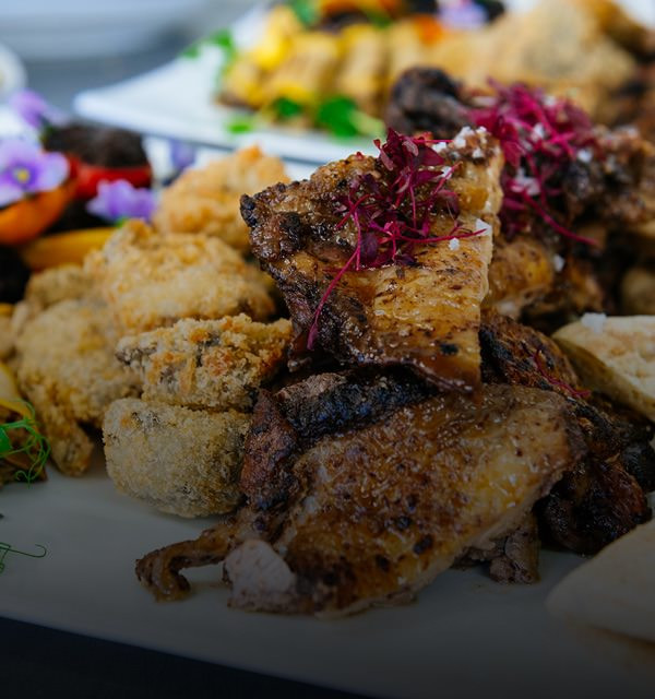 Wedding catering with grilled chicken and garnished with red cabbage on a beautifully laid out table.