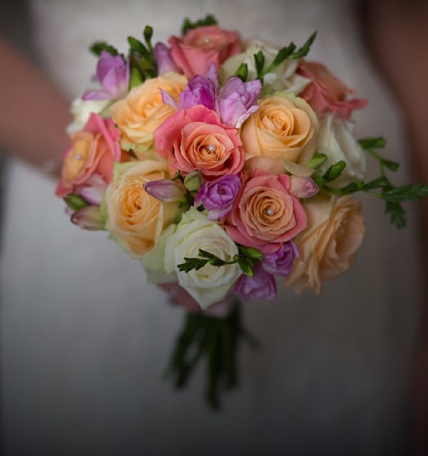 Bride holding a colourful bouquet of wedding flowers, containing white, orange and pink roses.