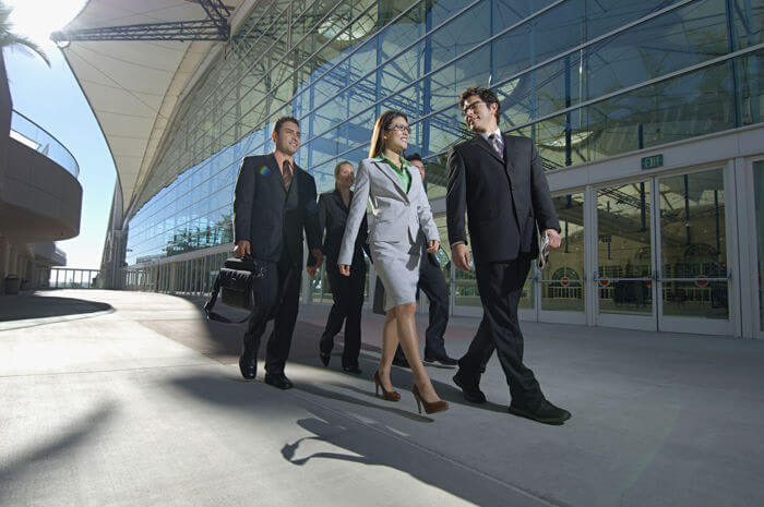 Executives, men and women, walking by a building