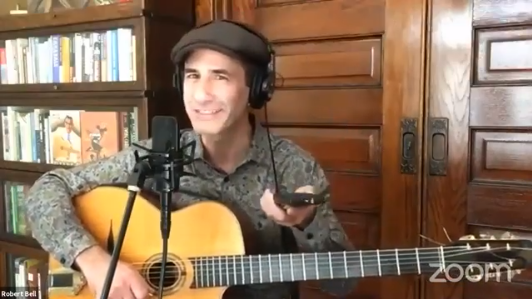 Robert Bell holding a guitar and pointing a remote control at livestream viewers while speaking into a microphone