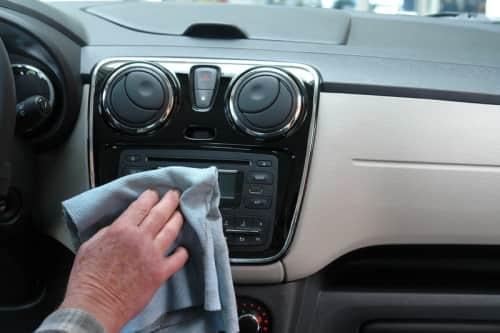 detailing the console of a car with a chamois cloth