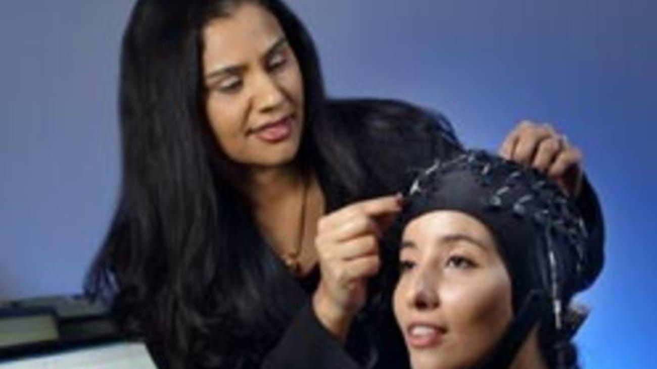 Vidya Kamath adjusts electrodes on a research assistant's head in preparation for measuring cortical responses in the brain as the subject describes an odor. Sniffin Sticks (foreground) are also used.
