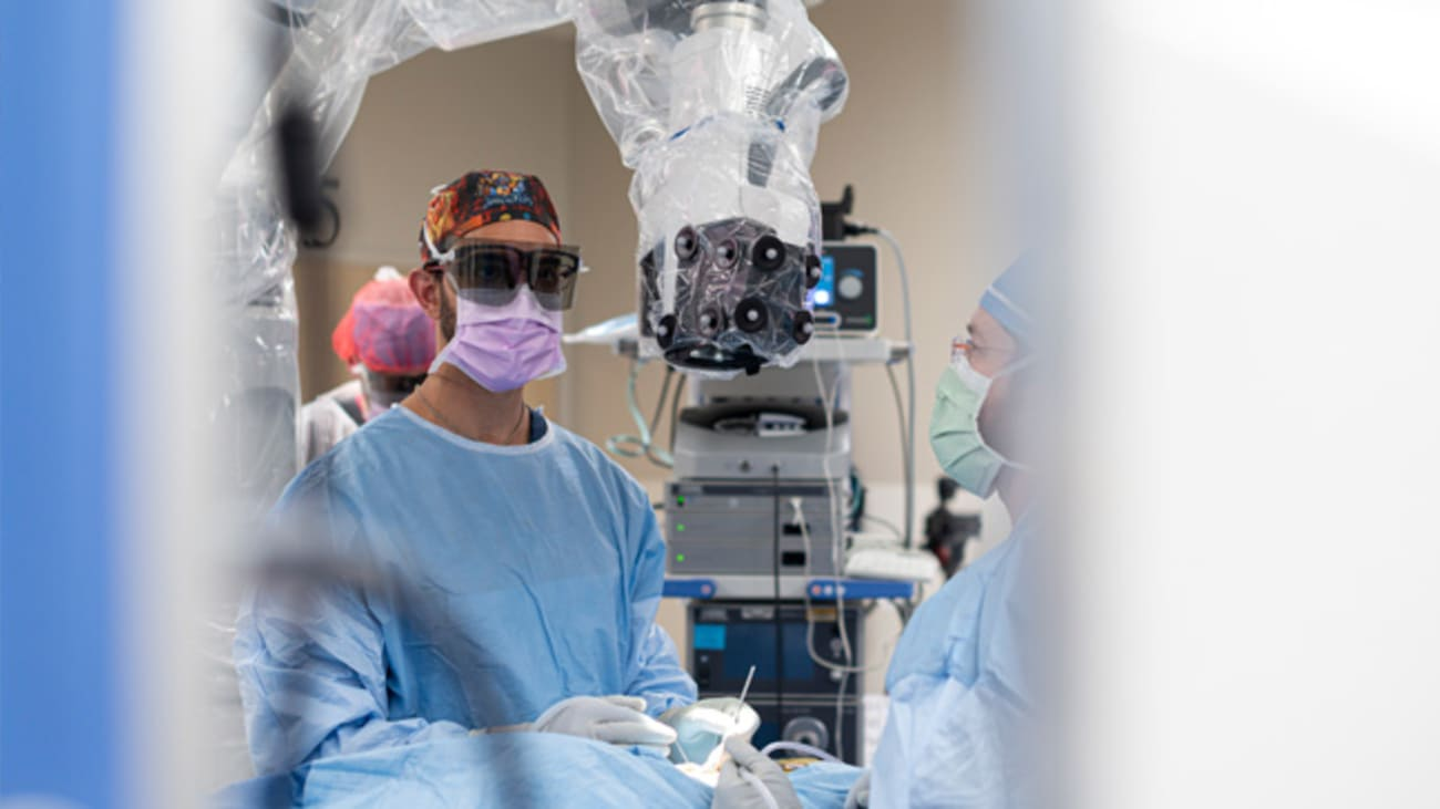 Ramin Eskandari, M.D., performs surgery using a Modus V digital robotic exoscope. With this device, he can look up at a screen instead of down into microscope eyepieces.