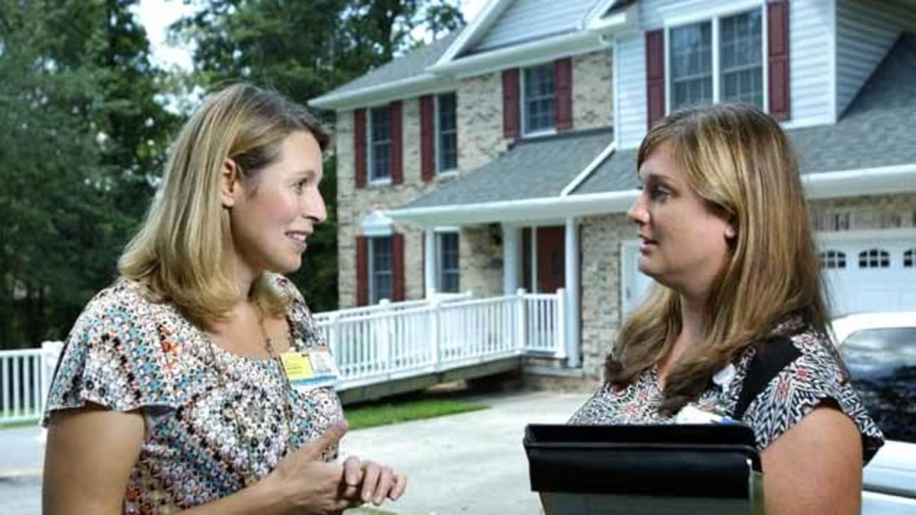 Quincy Samus, left, reviews a patient's care plan with memory care coordinator Kelly Marshall outside a client's home.