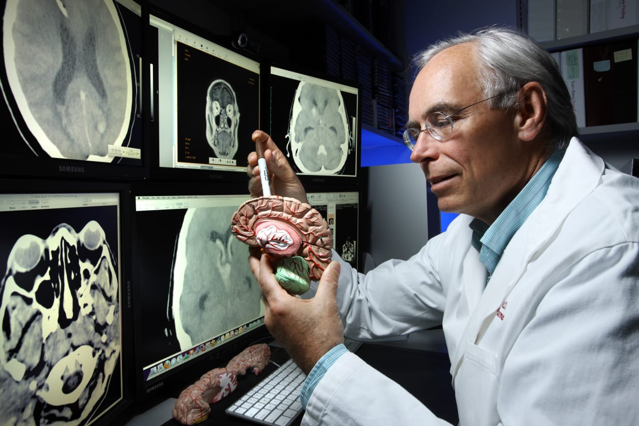 Dr. Dan Hanley holds a plastic brain model while facing computer monitors displaying brain images.
