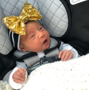 Kennedy Beck, a newborn baby, rests in a car seat as she goes home for the first time
