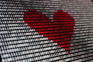 Concept image: Red heart shape superimposed over binary data on a computer display.