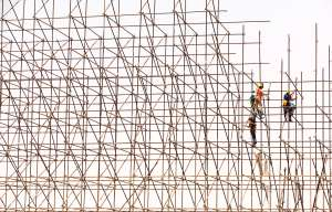 Scaffolding for a building, with construction workers climbing and working within