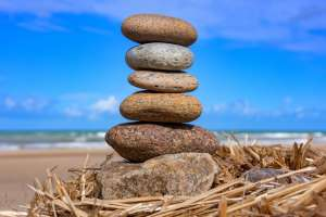 A stack of smooth stones on a beach near an ocean