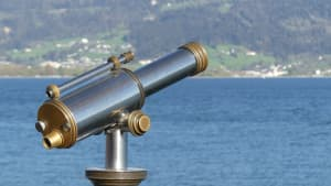 A binocular telescope on a stand near a body of water