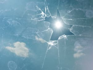 Broken window pane with sunlight shining through hole in glass