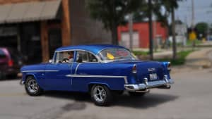 Stylized view of a deep blue 1955 Chevrolet Bel Air two-door automobile