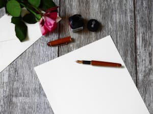 Writing concept - Fountain pen, white sheet of paper, open bottle of ink