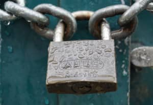 Security concept image: close-up view of rain-soaked padlocked chain on an outer door