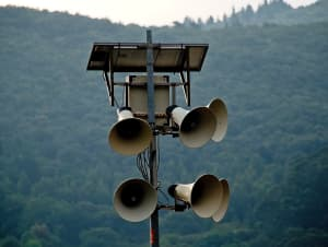 An array of public address speakers mounted on a pole