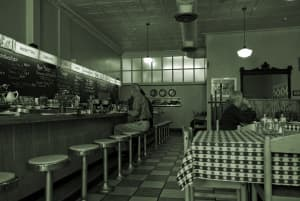 Duotone photo of a diner with customers waiting to be served