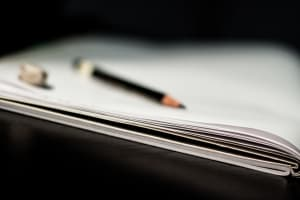Stylized photograph of notebook and, in blurry background, a pencil