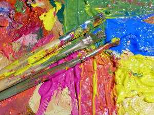 Paint brushes and colorful, splattered paint
