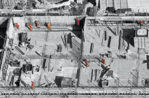 Construction site for a building, with construction workers climbing and working within