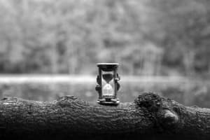 Monochrome photograph of an hourglass sitting on a tree log