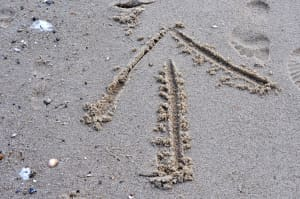 View from above of directional arrow in sand