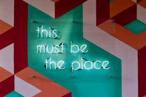 "Neon sign, ""This must be the place,"" mounted on a colorful grid pattern"