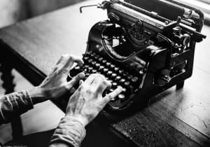 Monochrome photo of hands typing on an old typewriter