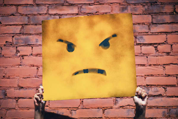 Hands holding up a sign showing an angry-face icon