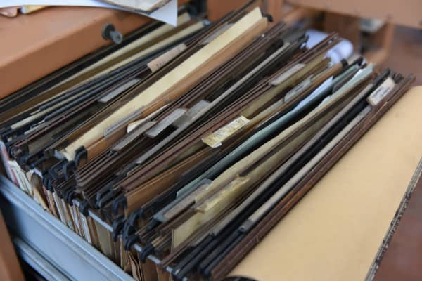 Worn and stained paper folders in an office desk drawer
