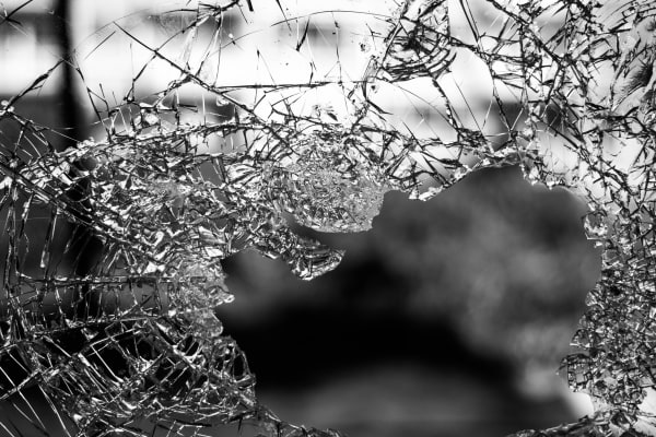 Monochrome image of a pane of glass out of which a hole has been broken