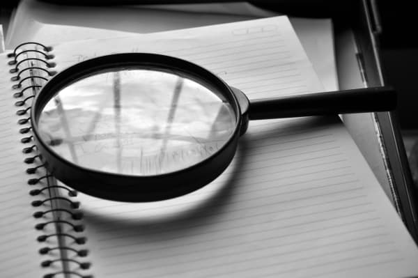 Monochrome photo of magnifying glass resting on an opened spiral notebook