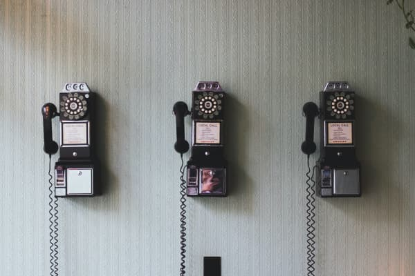 Communications concept - vintage pay telephones on a wall