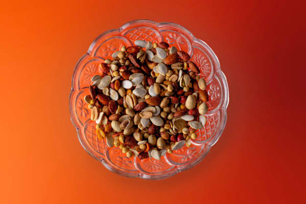 Overhead view of mixed nuts in a decorative glass dish on an orange surface