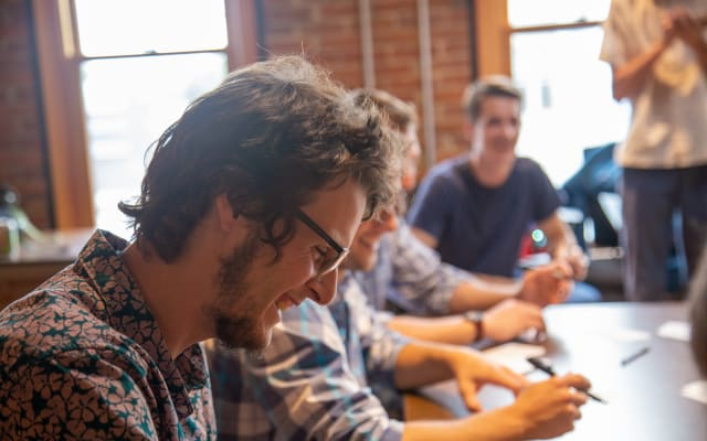 men smile as they sit doing UX