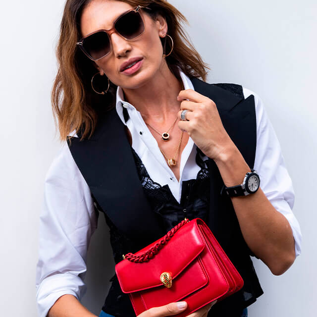 Model Nieves Alvarez wearing a Serpenti Forever Maxi Chain crossbody bag in Amaranth Garnet nappa leather, a Bvlgari Aluminium watch, Serpenti Heart sunglasses, and other B.zero1 jewels.