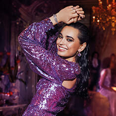 Partying model holding the Bvlgari Fantasia Veneta fragrance bottle in purple and red glass and the white Magnifying Essence flacon.